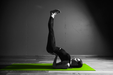 Black white photo of Young beautiful woman brunette in black clothes practice yoga in dark studio green mat Sport meditation monochrome