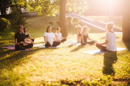 Group of young women practice yoga in park on summer sunny morning under guidance of instructor. Group of calm people is sitting in lotus pose on grass with closed eyes
