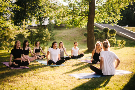 Group of smiling women prepare to meditation in park on summer sunny morning under guidance of trainer. Group of girl are sitting in lotus pose on yoga mats are relaxing talking before yoga training