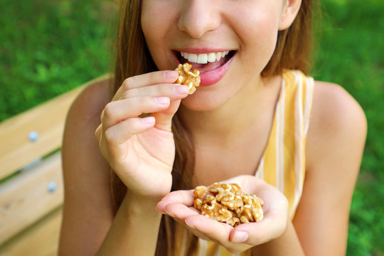 Close up of young woman eating walnuts in the park.