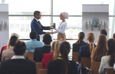 Businesswoman receiving award from businessman in a business seminar