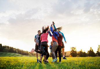 Large group of fit and active people jumping after doing exercise in nature. Wall mural