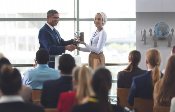 Businesswoman receiving award from businessman in a business seminar