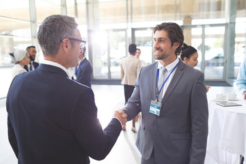 Business people shaking hand during a seminar
