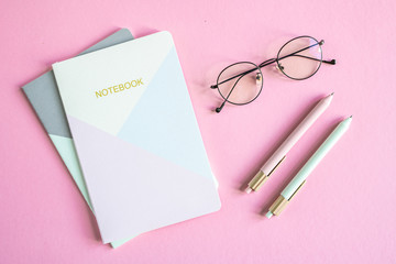 Top view of business person eyeglasses, two notebooks and pens