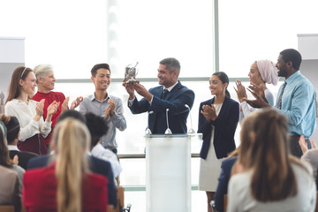 Businessman holding award at podium with colleagues in a business seminar
