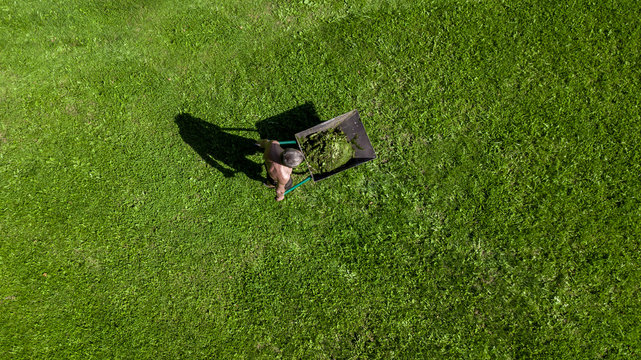 man pulls a wheelbarrow with garbage top view