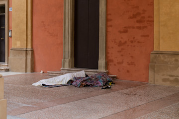 Poor homeless people or refugees sleeping on an urban street in the city, social documentary concept.