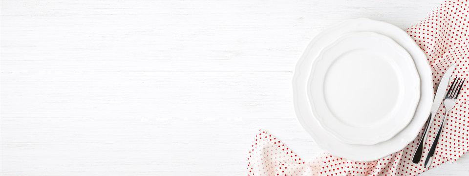 White empty plates on polka dot napkin.