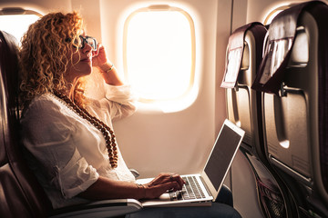 Business adult curly blonde woman travel on airplane connected to internet with modern computer laptop - people on work everywhere and digital nomad free lifestyle concept -flight on boad services