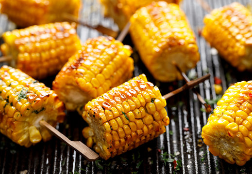Grilled corn on the cob with butter and  salt  on the grill plate, close-up