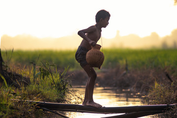 Asian little child fisherman holding fish trap walking along the river in the morning. Wall mural