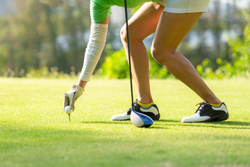 In de dag Ontspanning Hand asian sporty woman putting golf ball on tee with club in golf course on evening on time for healthy sport. Lifestyle and Sport Concept