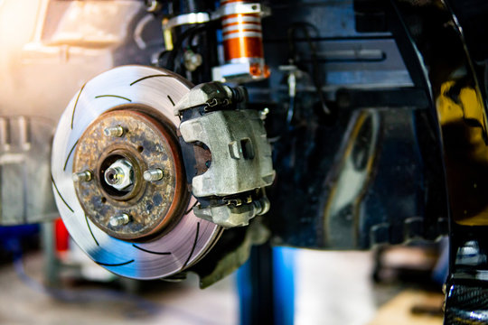 Disc brake and wheel bearing of racing car in auto repair garage. Automobile industry concept