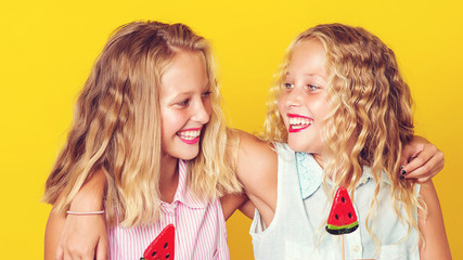 Happy girl friends hugging and laughing over yellow background. Friends having fun together. People, emotions, teens and friendship concept. Summer fashion
