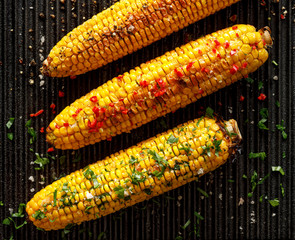 Grilled corn on the cob with butter, herbs, salt and aromatic spices on the grill plate, top view