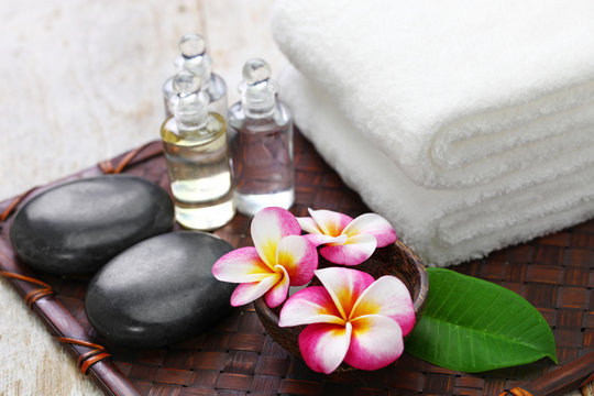 tropical spa resort concept; plumeria, hot stones, towels, and massage oils