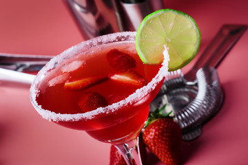 Strawberry red margarita alcoholic cocktail with tequila, liqueur, berries, lime juice, sugar and ice, pink background, copy space