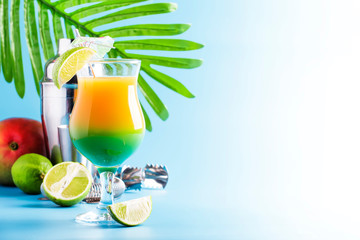 Double layer green yellow alcoholic cocktail with mango juice, rum, liqueur, lime and ice, blue background, copy cpase