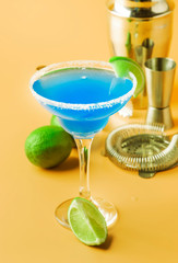 Blue margarita alcoholic cocktail with tequila, liqueur, lime juice, salt and ice, summer yellow background, copy space