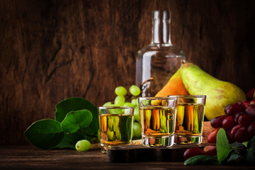 Rakija, raki or rakia - Balkan hard alcoholic drink or brandy from fermented fruits, old wooden table, still life, copy space