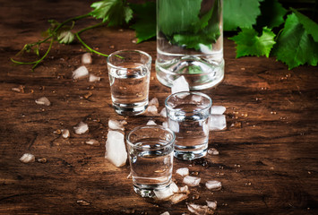 Cold vodka in shot glass, old wooden table, selective focus