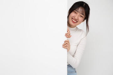 Smiling happy Asian woman standing behind big white poster isolated on white background
