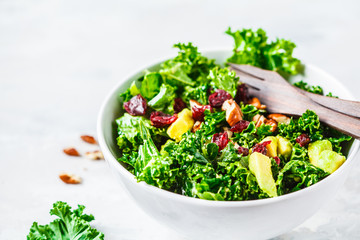 Green kale salad with cranberries and avocado in white bowl. Healthy vegan food concept.