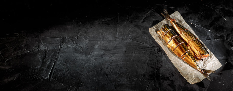 Delicious smoked fish on dark background.Top view with copy space