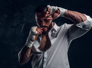 Handsome brutal man in protective boxing gloves is vering mouth guard while posing for photographer.