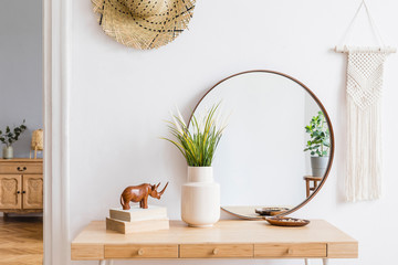 Sunny boho interiors of apartment with mirror, dressing table, furnitures, flowers, plants, rattan hat, sculpture, macrame and design accessories. Stylish home decor of open space. Template. Wall mural