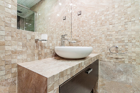 Interior of a modern pastel pink beige color bathroom, tiled mosaic walls and white round washbasin with mirror of the house
