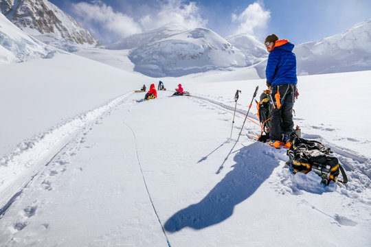 Climbers rest while towing sleds on the Kahiltna Glacier in the Alaska Range of mountains, Denali National Park, USA