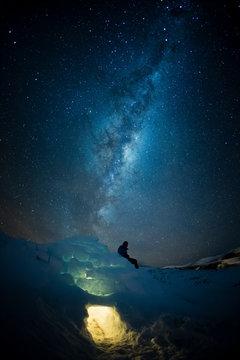 Woman sitting on igloo under Milky Way