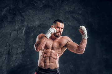 Muscular handsome fighter with naked torso is demonstraiting his power at dark photo studio.