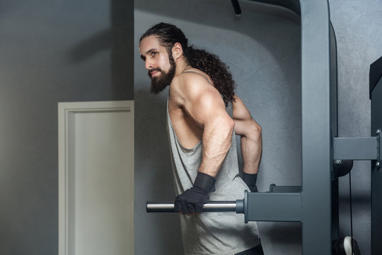 Portrait of powerful confident young adult strong man with long curly hair working out in gym, hanging on horizontal bar with hands, doing pull ups with, exercises for triceps. indoor, looking away