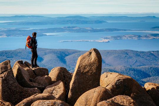 A woman is standing on rocks on the plateau of Mount Wellington, Hobart, Tasmania, Australia.