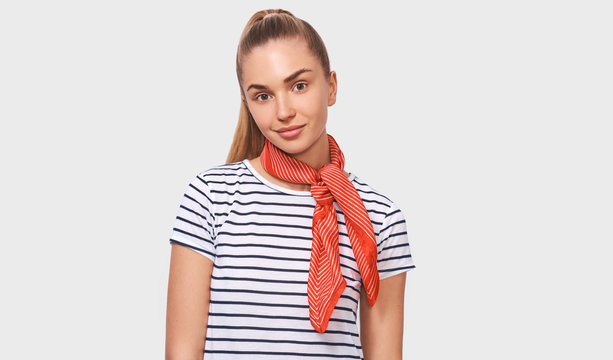 European charming young woman with ponytail hairstyle, wearing striped t-shirt, stylish red scarf on neck, looking to the camera posing over white studio background.