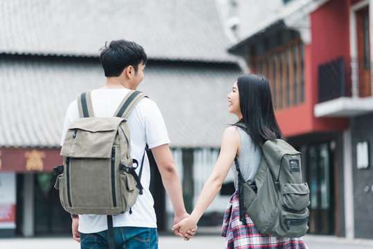 Traveler Asian backpacker couple feeling happy traveling in Beijing, China, cheerful young teenager couple walking at Chinatown. Lifestyle backpack tourist travel holiday in city concept.