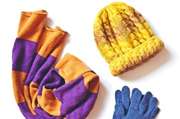 Striped orange and purple scarf, yellow knitted hat and blue woolen gloves on a white background. Flat lay winter fashion photo. Ladies clothes and accessories, knitwear