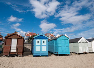Traditional wooden huts houses on the beach against blue sky and clouds in Southend on asea