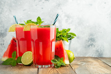Watermelon slushie with lime and mint, summer refreshing drink in tall glasses on a light background. Sweet cold smoothie with copy space