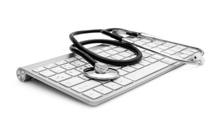 Computer keyboard with stethoscope on white.
