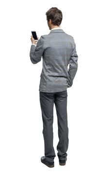 Back view of a businessman who is looking into the smartphone.