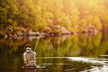 Papiers peints Peche Fisherman using rod fly fishing in mountain river autumn splashing water