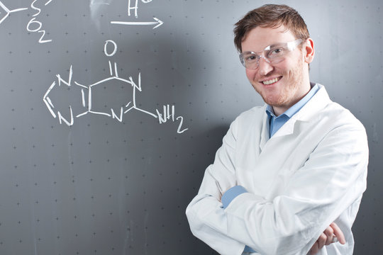 Germany, Portrait of young scientist standing next to chemical equation on chalk board, smiling