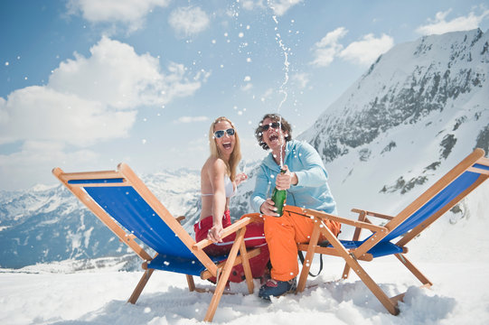 Austria, Salzburger Land, Young couple celebrating with champagne, laughing, portrait