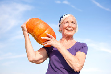 Germany, Saxony, Senior woman carrying pumpkin on shoulder