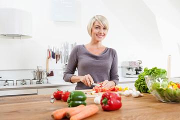 Germany,Bavaria,Munich,Woman preparing food in kitchen