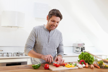 Germany, Bavaria, Munich, Man chopping vegetables in kitchen